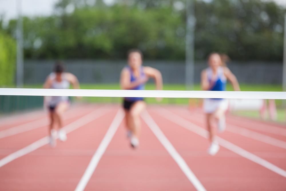 JPG Female athletes running towards finish line on track field