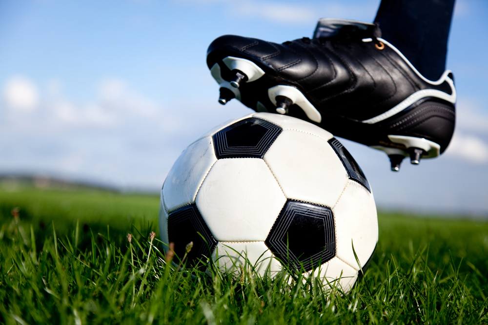 Football or soccer ball at the kickoff of a game - outdoors