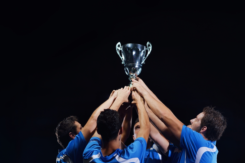 Jpgsoccer players team group celebrating the victory and become champion of game while holding win cup